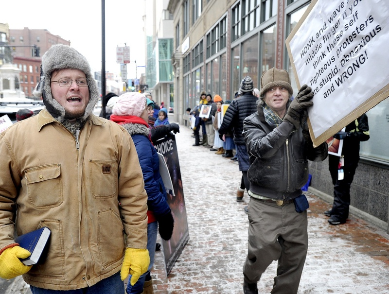 Portland businessman Mike Fink, right, passes anti-abortion Pastor Jeremy Hiltz of Chelsea during a counter-protest on Congress Street in Portland in January. Fink said Monday he is closing his nearby deli because of the effect of the weekly protests on his business.