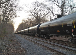 A Pan Am Railways freight train moves through the Riverton neighborhood of Portland, bearing a red placard that indicates it is carrying crude oil. A federal hearing Wednesday was intended to give interest groups and the public a chance to comment generally on the transportation of hazardous materials via rail.