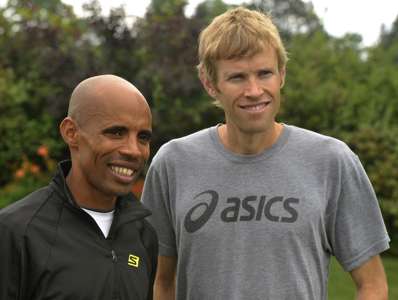Elite runners Meb Keflezighi and Ryan Hall pose for photos following a Beach to Beacon news conference Friday.