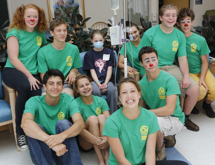 Makenzie Tompkins, 11, of Old Orchard Beach poses for a photo with members of Circus Smirkus Big Top Tour as they make a stop at The Barbara Bush Children's Hospital on Sunday.