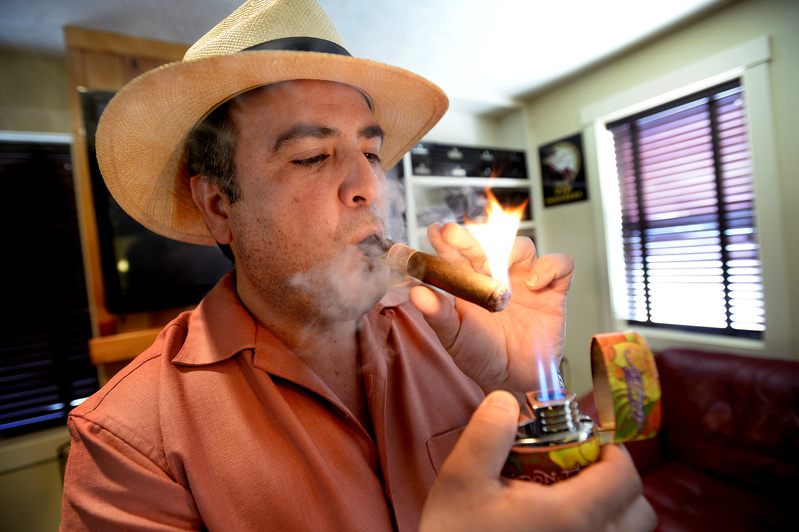 Daniel Vela, owner of Saco River Cigars on Middle Street in Saco, lights up a cigar in his lounge Wednesday. Vela believes a bottle club will complement the neighborhood because it will bring in people who are spending money at nearby restaurants and shops.