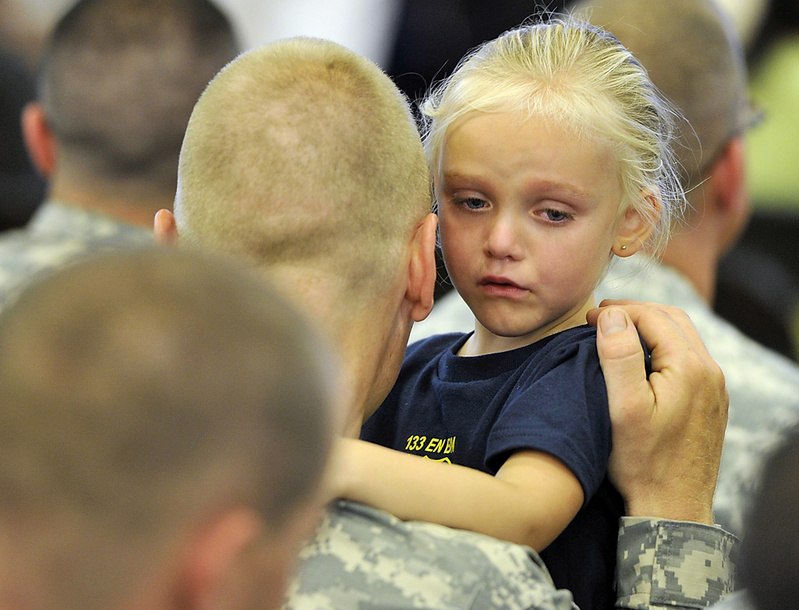 Sgt. Mark Thibeault listens to the words of his emotional daughter, Tatyanah, 3, prior to the start of Saturday's send-off ceremony for the 133rd Engineer Battalion and 1035th Engineer Survey and Design Team.