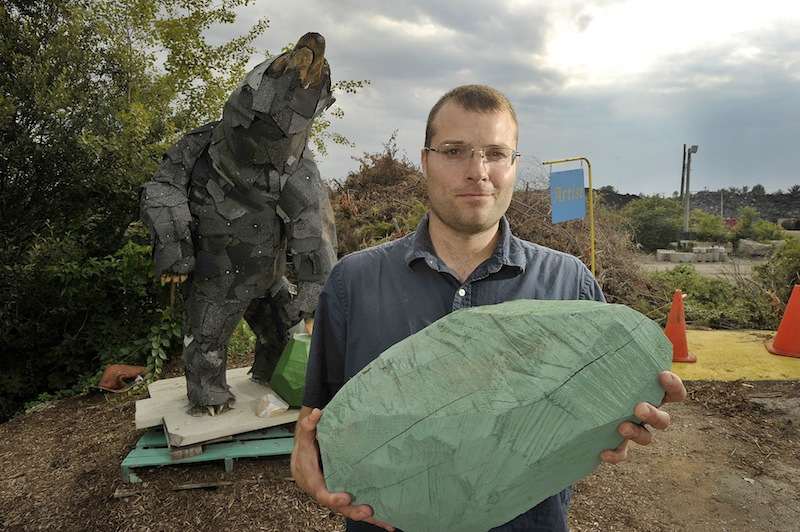 """Local artist Andy Rosen is completing an artist-in-residency at the Scarborough Recycling Center. He has created a 7-foot-tall black bear out of found materials at the dump. Rosen is holding one of the wooden """"rocks"""" he made for the exhibit."""