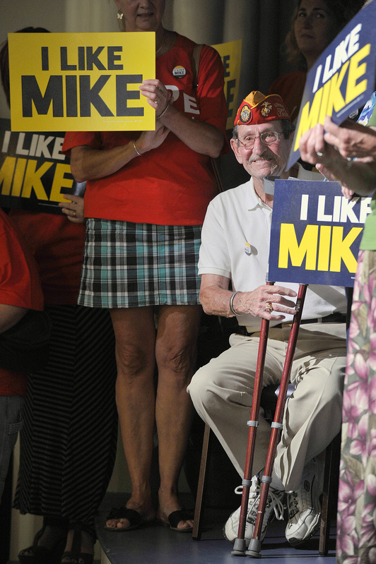 "Maurice ""Mo"" Marquis, wearing a Marine Corps League cap, shows his approval of U.S. Rep. Mike Michaud's run for governor at the Franco-American Heritage Center in Lewiston on Thursday. The Democrat's rivals, incumbent Republican Gov. Paul LePage and independent Eliot Cutler, promise a challenging race."