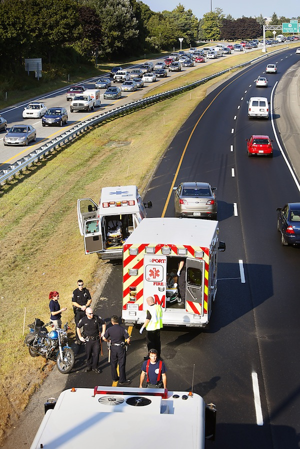 Rescue personnel respond to a motorcycle crash on the northbound lane of Interstate 295 near the Deering Avenue overpass in Portland on August 27, 2013.
