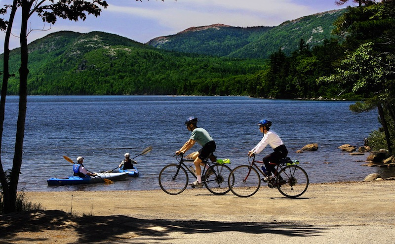 """Bikers cruise along a path while kayakers set off by Eagle Lake in Acadia National Park on Mt. Desert Island, Maine, in this Tuesday, June 21, 2005 file photo. Mount Desert Island, which is linked to mainland Maine by a two-lane bridge, is ranked 25th in Travel & Leisure magazine's article, """"World's Best Islands."""" (AP Photo/Pat Wellenbach)"""