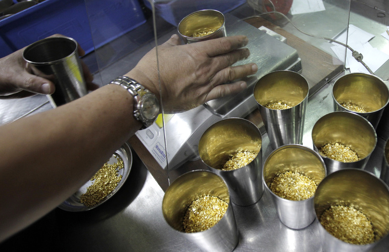 A technician prepares containers of gold grains for melting into in Dubai, United Arab Emirates.