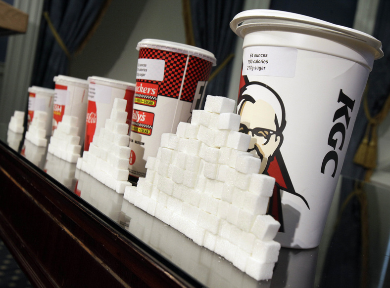 Various sizes of soft drink cups are displayed next to stacks of sugar cubes. A new study using mice found that the mouse equivalent of just three sugary sodas a day had significant negative effects on life span and competition for mates.