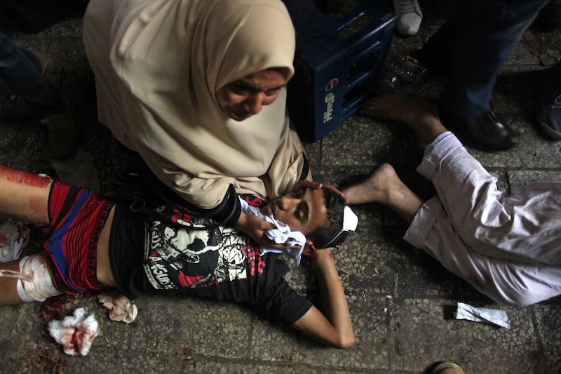 Egyptians lay on the ground after being injured during clashes between security forces and supporters of Egypt's ousted President Mohammed Morsi in Ramses Square, near the Al-Fath mosque, in Cairo, Egypt, Friday, Aug. 16, 2013. Gunfire rang out over a main Cairo overpass and police fired tear gas as clashes broke out after tens of thousands of Muslim Brotherhood supporters took to the streets Friday across Egypt in defiance of a military-imposed state of emergency following the country's bloodshed earlier this week. (AP Photo/Khalil Hamra)