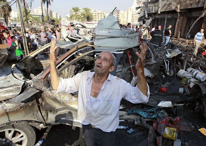 A man recites prayers amid the destruction after a car bomb exploded outside the Al-Taqwa mosque in the northern city of Tripoli, Lebanon, on Friday.