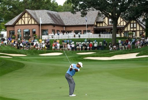 Tiger Woods hits to the 18th green during a practice round Tuesday for the PGA Championship golf tournament at Oak Hill Country Club in Pittsford, N.Y.