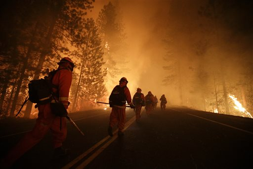 Inmate firefighters walk along state Highway 120 as crews continue to battle the Rim Fire near Yosemite National Park, Calif., on Sunday. Fire crews are clearing brush and setting sprinklers to protect two groves of giant sequoias.