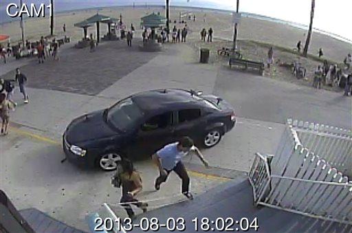 In this still frame made from security camera footage from Snapchat, Inc. headquarters, pedestrians scatter as a car drives through a packed afternoon crowd along the Venice Beach boardwalk in Los Angeles, Saturday, Aug. 3, 2013. A driver plowed into crowds at the Venice Beach boardwalk in a seemingly intentional hit-and-run that killed a woman and injured 11 others.