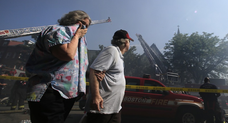 Janice Smythe covers her face as she walks through smoke with John Malone while passing a five-alarm blaze at St. John the Baptist Albanian Orthodox Church in South Boston on Wednesday.