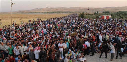 In this photo provided by the U.N. High Commissioner for Refugees and taken on Thursday, Aug. 15, 2013, Syrian refugees cross the border toward Iraq at the Peshkhabour border point at Dahuk, 260 miles northwest of Baghdad.