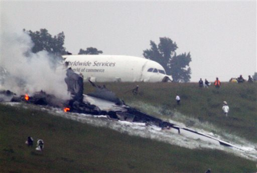 Debris burns as a UPS cargo plane lies on a hill at Birmingham-Shuttlesworth International Airport in Birmingham, Ala., about a half-mile north of Runway 18.