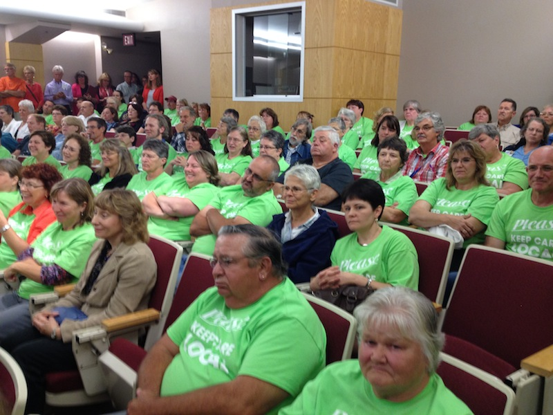"""Hundreds of people attended a public hearing in Auburn on Thursday, Aug. 29, 2013 to testify against a proposed partnership between insurer Anthem Blue Cross and Blue Shield and MaineHealth. Scores of people waiting to speak wore neon green t-shirts with the slogan """"Keep care local."""""""