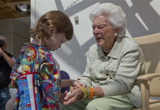 Avery Garrison, 3, of Scarborough examines bracelets worn by former first lady Barbara Bush on Thursday at The Barbara Bush Children's Hospital at Maine Medical Center in Portland.