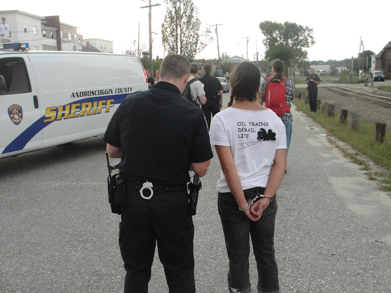"""Three people were arrested Wednesday, Aug. 28, 2013 after staging an oil-train protest on railroad tracks in downtown Auburn. The back of one of the protestors' shirts says, """"Oil trains derail life."""""""