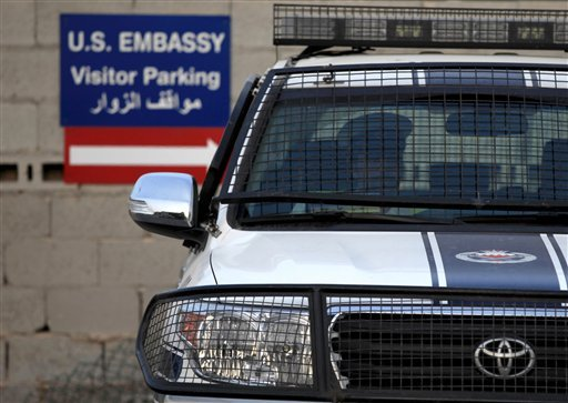In this Aug. 6 photo, a Bahraini police officer sits in a police car at a new checkpoint near the U.S. Embassy in Manama, Bahrain. (AP Photo/Hasan Jamali)