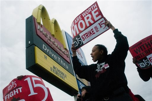 """Fast-food worker Michelle Osborn, 23, of Flint shouts out chants as she and a few dozen others strike outside of McDonald's on Wednesday, July 31, 2013 in Flint. Some fast food restaurant workers have walked off the job in the Detroit area as part of an effort to push for higher wages. Organizers say they began the walkout at restaurants in Lincoln Park and Southfield on Tuesday night. Workers in Flint hit the street Wednesday outside a McDonald's, saying they want wages """"super-sized."""" Workers want $15 and hour, better working conditions and the right to unionize. The restaurant industry says higher wages would hurt job creation. The actions follow strikes this week in other parts of the country. (AP Photo/The Flint Journal, Jake May)"""
