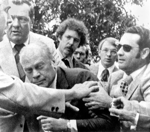 """In this Sept. 5, 1975, photo, President Gerald Ford is shielded by the Secret Service after an assassination attempt by Lynette """"Squeaky"""" Fromme. Ford had spoken at a """"Host Breakfast,"""" and was walking to California's state Capitol in Sacramento when the attempted assassination took place."""