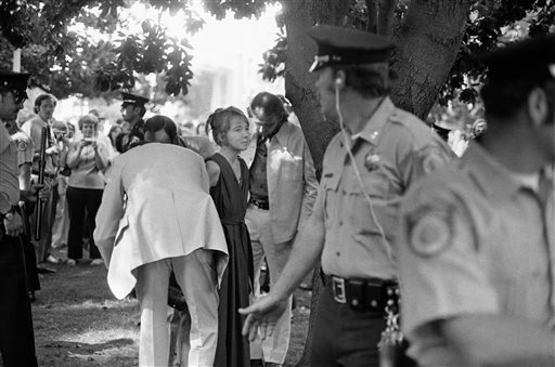 """Lynette """"Squeaky"""" Fromme is taken into custody. Fromme, a devoted follower of the infamous Charles Manson, wearing a red robe, stepped out from behind a tree and pointed a loaded pistol at the president."""
