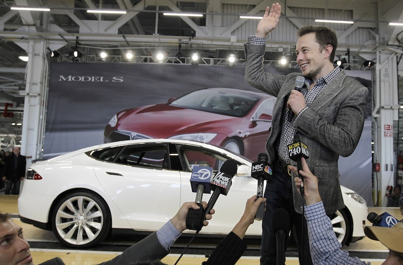 """In this June 22, 2012 file photo, Tesla CEO Elon Musk waves during a rally at the Tesla factory in Fremont, Calif. Musk on Monday, Aug. 12, 2013 unveiled a concept for a transport system he says would make the nearly 400-mile trip in half the time it takes an airplane. The """"Hyperloop"""" system would use a large tube. Inside, capsules would float on air, traveling at over 700 miles per hour. (AP Photo/Paul Sakuma, File)"""