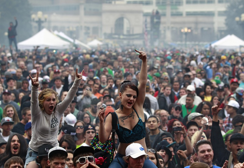 In this April 20, 2013 file photo, members of a crowd numbering tens of thousands smoke marijuana and listen to live music, at the Denver 420 pro-marijuana rally at Civic Center Park in Denver. The U.S. government said Thursday, Aug. 29, 2013 that the federal government will not make it a priority to block marijuana legalization in Colorado or Washington or close down recreational marijuana stores, so long as the stores abide by state regulations. (AP Photo/Brennan Linsley, File)
