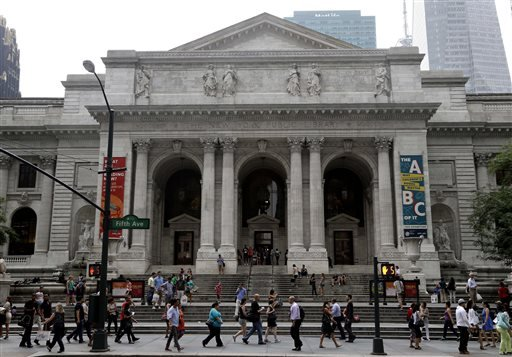 Pedestrians walk past the entrance to the main branch of the New York Public Library.