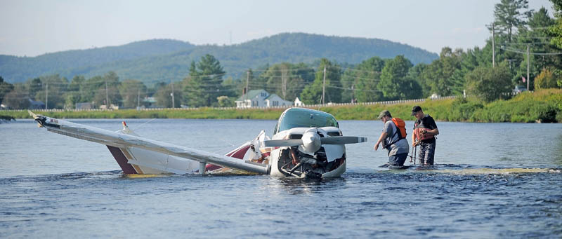 Charles Robins, left, of Charlie and Sons garage and Chad Robertson, right, with the Maine Warden Service prepare to haul a single-engine Beechcraft airplane from the Kennebec River after it crashed shortly after takeoff from Gadabout Gaddis Airport in Bingham today.