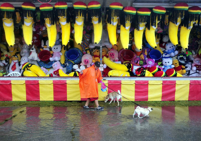 Carol Deshenes walks with her dogs, Cote and Princess, as rain falls on the 195th annual Skowhegan State Fair at the Skowhegan Fairgrounds today.