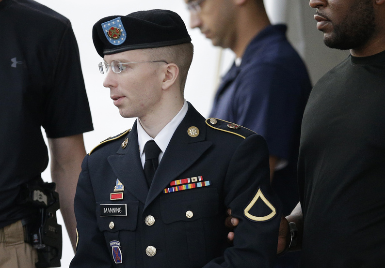 Army Pfc. Bradley Manning is escorted to a waiting security vehicle outside of a courthouse in Fort Meade, Md., last month.