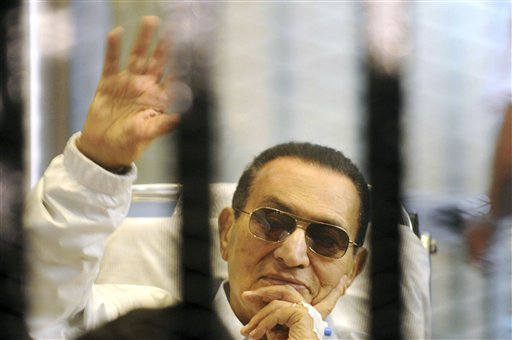 Former Egyptian President Hosni Mubarak waves to his supporters from behind bars as he attends a hearing in his retrial on appeal in Cairo in this April 13, 2013, photo.