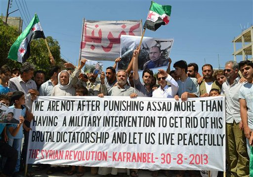 This citizen journalism image provided by Edlib News Network, ENN, shows anti-Syrian regime protesters carrying a banner during a demonstration in Kafr Nabil town, in Idlib province, northern Syria, on Friday, Aug. 30, 2013.