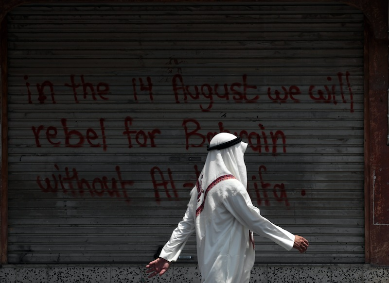 A Bahraini man walks past a closed shop sprayed with graffiti against the ruling Al Khalifa family in the western village of Karzakan, Bahrain, Wednesday, Aug. 14, 2013. Opposition groups launched a fresh push against the Gulf monarchy on Wednesday, an effort to revitalize their two-and-a half-year-old pro-democracy uprising. (AP Photo/Hasan Jamali)