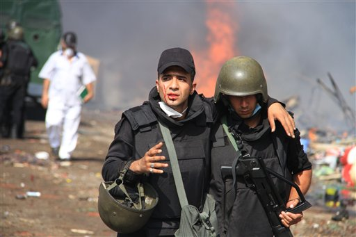 A member of the Egyptian security force carries another as they clear a sit-in camp set up by supporters of ousted Islamist President Mohammed Morsi in Nasr City district, Cairo, Egypt, on Wednesday.