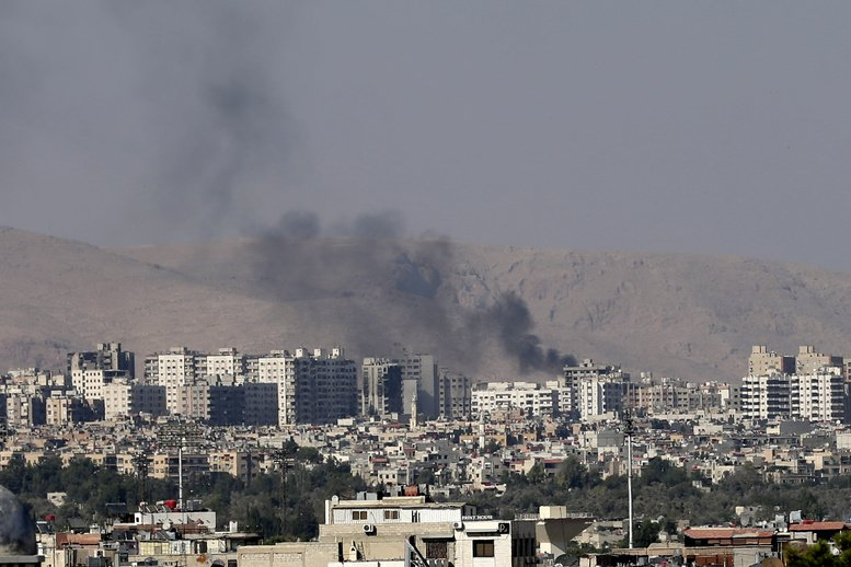 Black columns of smoke rise from heavy shelling in Barzeh, a suburb of Damascus, Syria, on Friday.