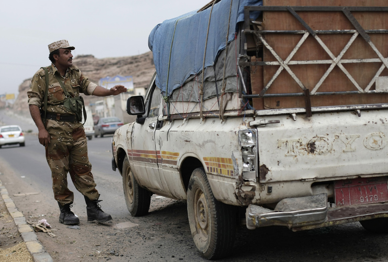 A Yemeni soldier stops a car at a checkpoint in a street leading to the U.S. embassy in Sanaa, Yemen, on Sunday. Security forces closed access roads, put up extra blast walls and beefed up patrols near some of the U.S. diplomatic missions in the Muslim world that Washington ordered closed.