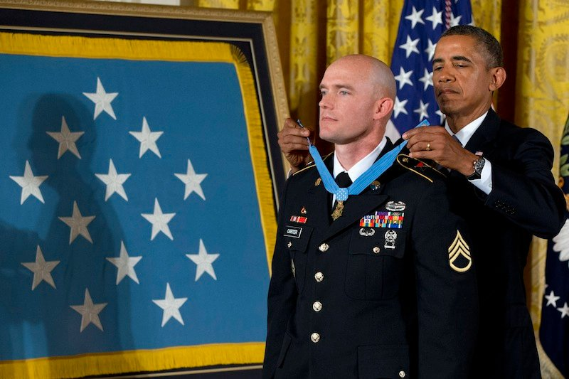 President Barack Obama awards US Army Staff Sgt. Ty M. Carter the Medal of Honor for conspicuous gallantry, Monday, Aug. 26, 2013, during a ceremony in the East Room of the White House in Washington. Carter received the medal for his courageous actions while serving as a cavalry scout with Bravo Troop, 3rd Squadron, 61st Cavalry Regiment, 4th Brigade Combat Team, 4th Infantry Division, during combat operations in Kamdesh District, Nuristan Province, Afghanistan on Oct. 3, 2009. Carter is the fifth living recipient to be awarded the Medal of Honor for actions in Iraq or Afghanistan. (AP Photo/Jacquelyn Martin)