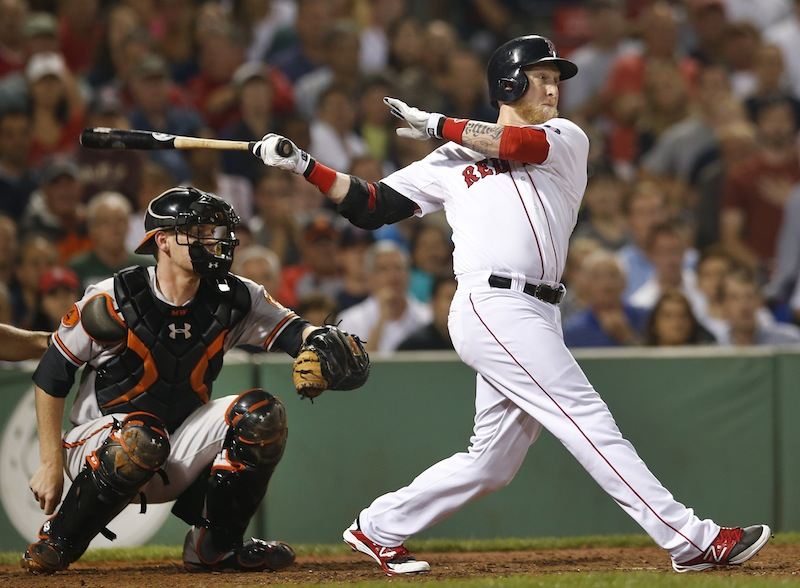 Boston's Mike Carp hits a pinch-hit single to drive in a run as Baltimore Orioles catcher Matt Wieters watches in the eighth inning at Fenway Park in Boston on Wednesday. It proved to be the winning run as the Red Sox won 4-3.
