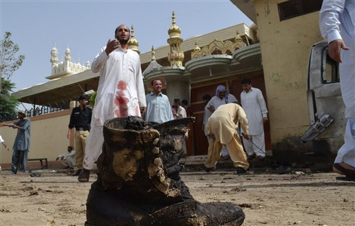 Pakistani investigators collect evidence at the site of a bomb attack in Quetta, Pakistan on Thursday. A suicide bomber attacked a funeral for a policeman in southwestern Pakistan, killing dozens of people, including a senior police officer, and wounding over 60, police said.