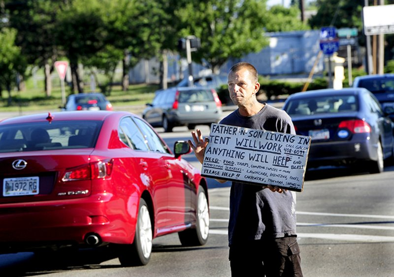 Galen Jordan panhandles – legally – at the corner of High Street and Forest Avenue in Portland early Thursday. Police were to begin enforcing a new ordinance Thursday that prohibits panhandling in roadway medians.