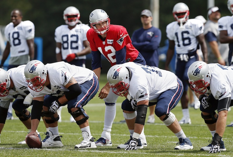 New England Patriots quarterback Tom Brady (12) waits for a snap behind the offensive line during NFL football practice in Foxborough, Mass., Monday, Aug. 19, 2013. (AP Photo/Michael Dwyer)