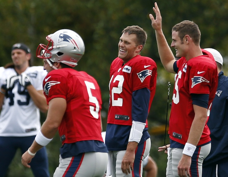 New England Patriots football quarterbacks Tom Brady, center, Ryan Mallett, right, and Tim Tebow (5) laugh together during team practice in Foxborough, Mass., Monday, Aug. 26, 2013. (AP Photo/Elise Amendola)