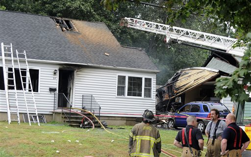 Firefighters stand at the scene of a plane crash Friday in East Haven, Conn.