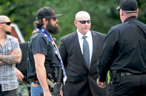 Gilberton Police Chief Mark Kessler, center, talks with members of the Constitutional Security Force outside Borough Hall in Gilberton, Pa., last month. Kessler says he expects to be fired for posting incendiary videos in which he rants obscenely about the Second Amendment and liberals while spraying machine-gun fire with borough-owned weapons.