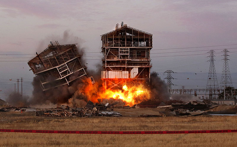One of the remaining towers comes down Saturday at the decommissioned Kern Power Plant in Bakersfield, Calif. Five spectators were injured, including a man whose leg was severed, when shrapnel was sent flying, police said. More than 1,000 people had gathered at 6 a.m. in a nearby parking lot to watch the planned implosion. PGE Implosion