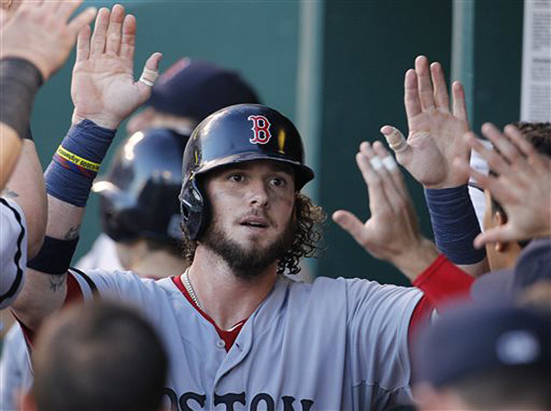 Jarrod Saltalamacchia is welcomed by his teammates in the Boston Red Sox dugout Saturday night after scoring on a Will Middlebrooks single in the fourth inning of a 5-3 victory against the Kansas City Royals.