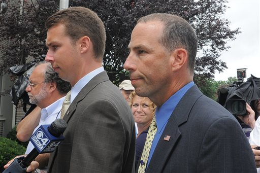 Massachusetts State Police Sgt. Sean Murphy, right, a tactical photographer, and his son Connor Patrick Murphy, arrive at State Police Headquarters in Framingham for his hearing to determine his duty status after he released images of the arrest of the Boston Marathon bombing suspect in this July 23, 2013, photo.